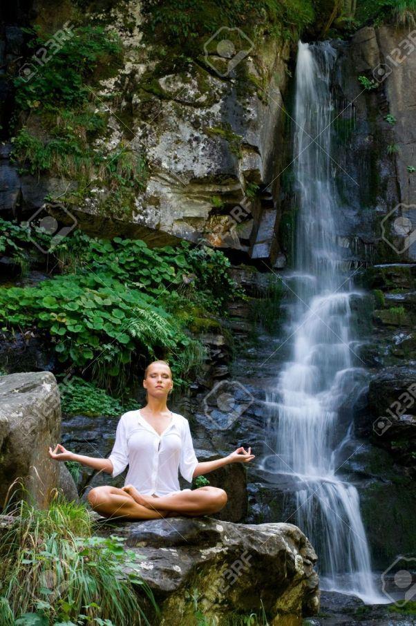 8235416-Joven-y-bella-mujer-meditando-en-posici-n-de-loto-mientras-hace-yoga-en-la-naturaleza-cerca-de-casca-Foto-de-archivo