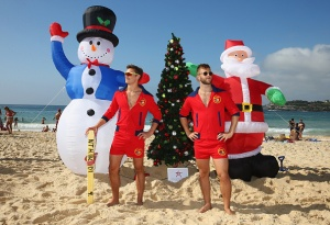SYDNEY, AUSTRALIA - DECEMBER 25: North Bondi surf-club life-savers wear 'Baywatch-style' uniforms as they pose in front of their Christmas decorations at Bondi Beach on December 25, 2014 in Sydney, Australia. Bondi Beach is a popular tourist destination on Christmas Day. (Photo by Don Arnold/Getty Images)