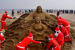 Artists dressed as Santa Claus create a Santa Claus sculpture on the eve of Christmas Puri golden beach, 67 kilometers (42 miles) from the eastern city of Bhubaneswar, India, Saturday, Dec. 24, 2011. Christmas Day is observed as a national holiday in India. (AP Photo/Biswaranjan Rout)